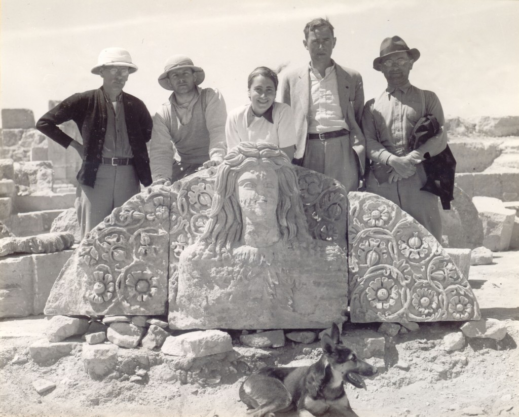 Caption: Clarence Fisher, Carl Pape, Helen Glueck, Nelson Glueck, and S.J. Schweig pose behind the goddess sculpture, while Atarah reclines in front.