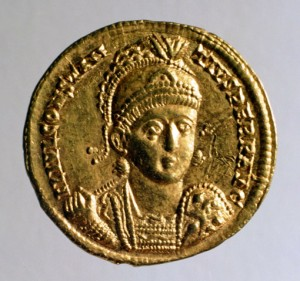 Gold solidus of Constantius II, with the bust of the emperor wearing military dress and helmet, with a spear and shield. 351–355 CE.