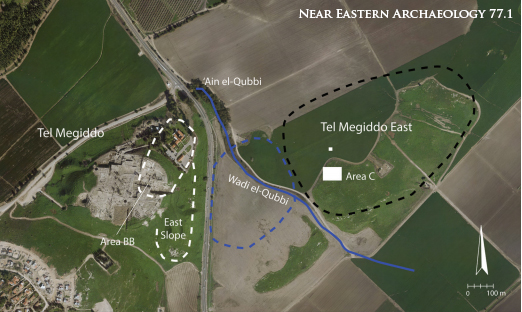 The dual site of Early Bronze Age I Megiddo. Tel Megiddo on the west, with estimated EB I size in white dashed lines, and Tel Megiddo East, with estimated  boundaries in black dash. The blue line represents the wadi cut by run-off from the local water source at 'Ain el-Qubbi, and the blue dashed line is a reconstruction of the  location of the EB I marsh identified in JVPR excavations. Aerial Orthophoto of Jezreel Valley, Israel. Israel: Ofek Aerial Photography Ltd., January-February 2011.
