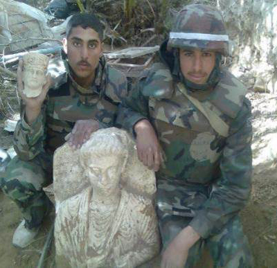 Looted funerary bust from Palmyra flanked by two Syrian soldiers. Photo courtesy Michel al-Maqdissi.