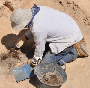 Close-up of John Mark Wade uncovering ashy layer.