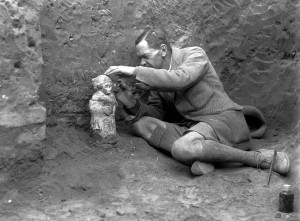 Sir Leonard Woolley carefully excavating a statuette depicting a worshipper.  The statuette was placed in a small Old Babylonian chapel dedicated to the god Hendursag. © The Trustees of the British Museum.
