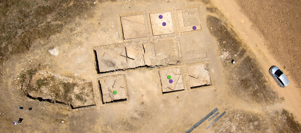 Khirbet Summeily at the end of excavations in July 2014. Violet dots mark the findspots of bullae found in Phase 5 or in sub-floor foundation deposits of Phase 4. Green dots mark the findspots of bullae in later phases. North is generally toward the top of the page. Photograph by W. Isenberger and D. Farrow for the Hesi Regional Project.