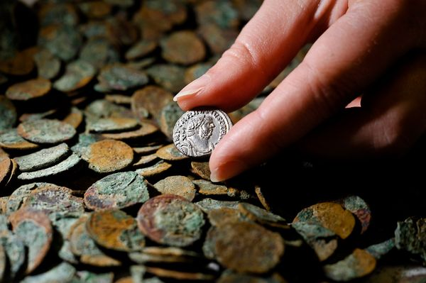 Hand holding ancient coin.